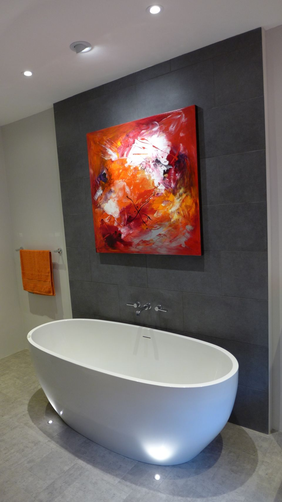 interior design in Bath - here, a freestanding bath with grey tiled feature wall and bathroom art beautifully illuminated
