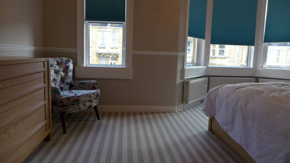 bedroom with striped carpet and blue blinds