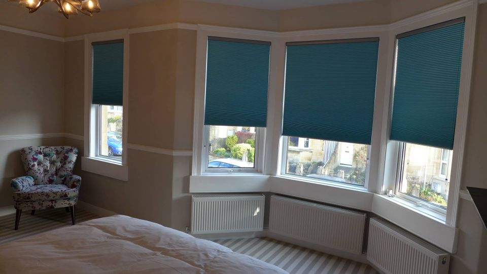 bedroom with teal pleated blinds