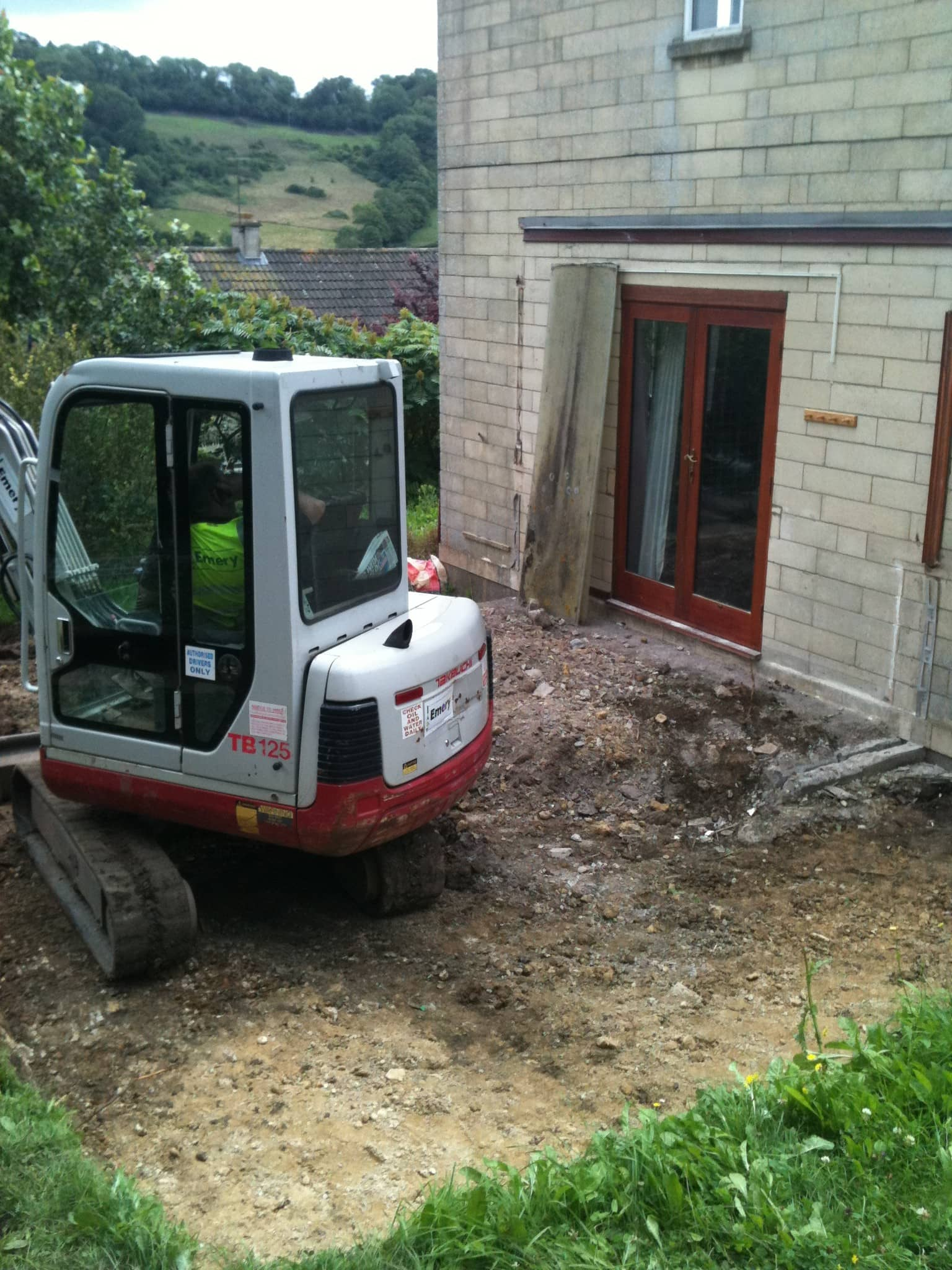 digger demolishes old conservatory