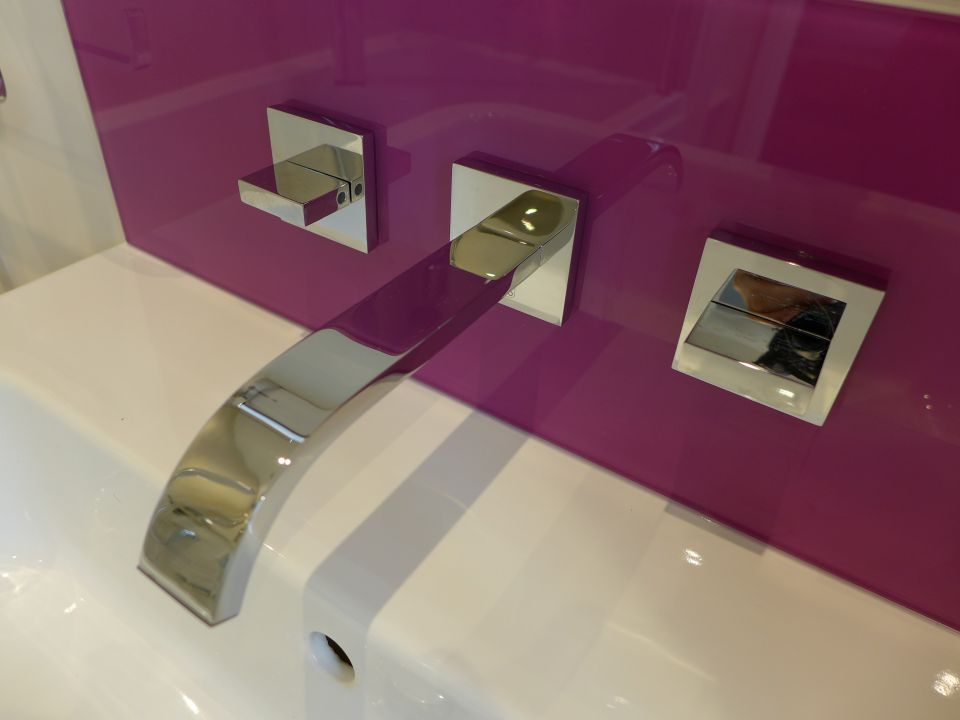 wall mounted basin taps in purple glass splashback