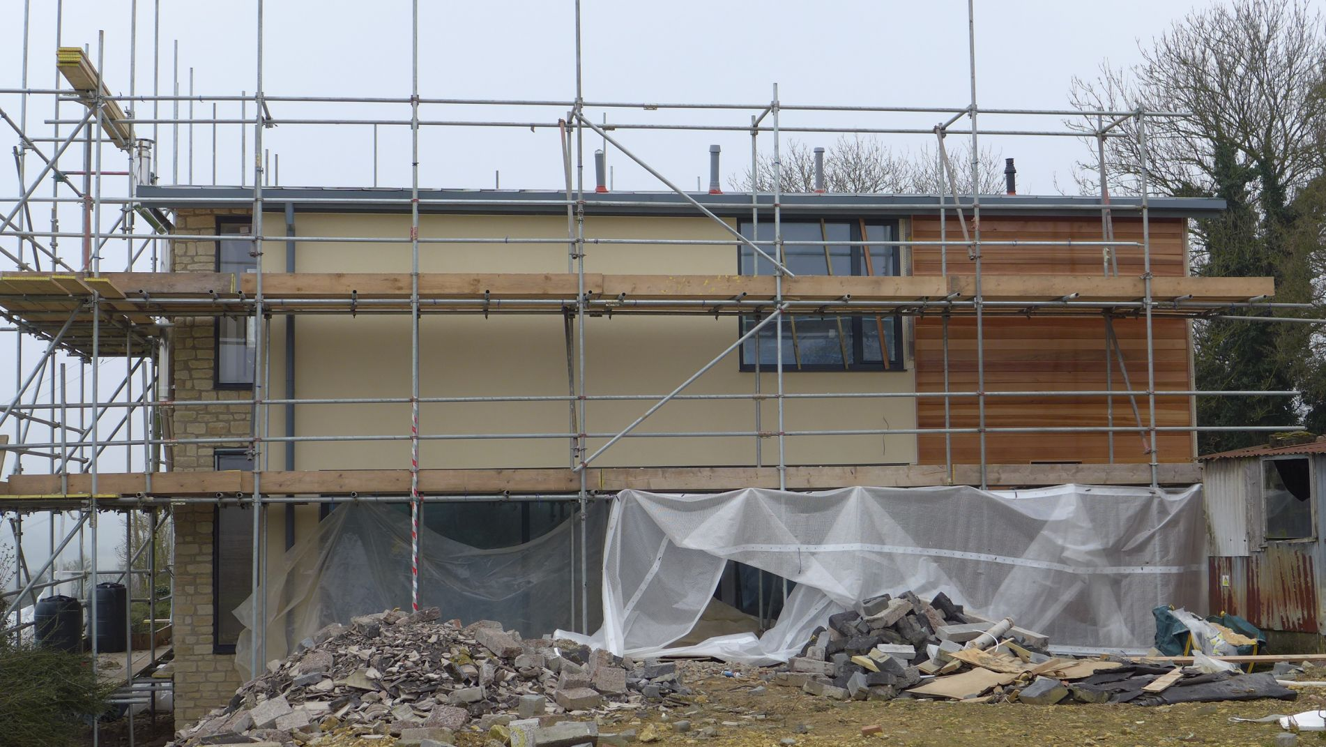 new build with timber cladding and rough stone