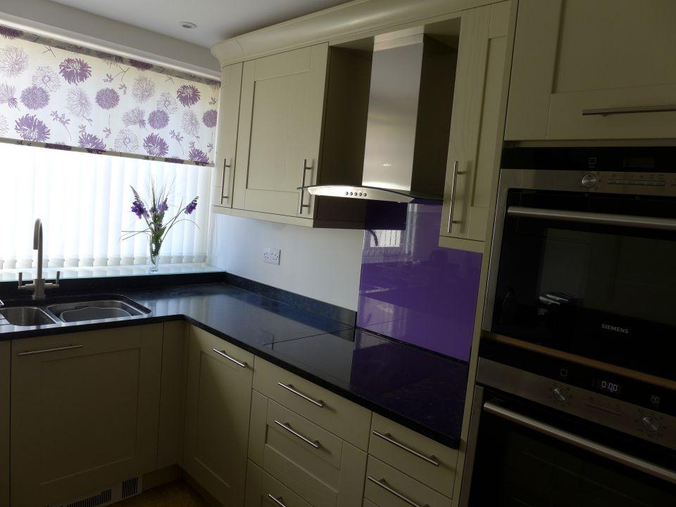 small kitchen with purple splashback