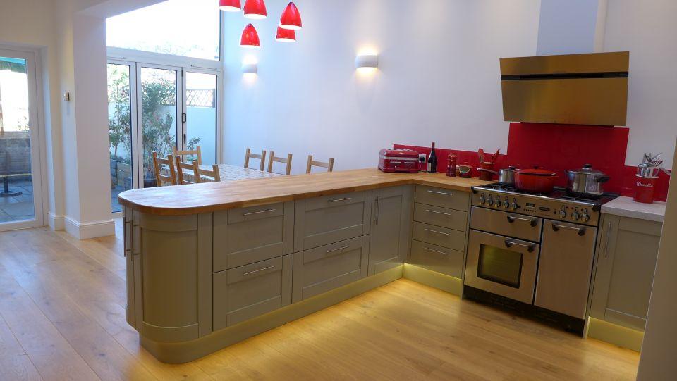 green kitchen design in Bath with red splashback