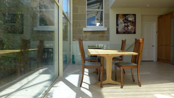 dining area in glass extension bathed in sun
