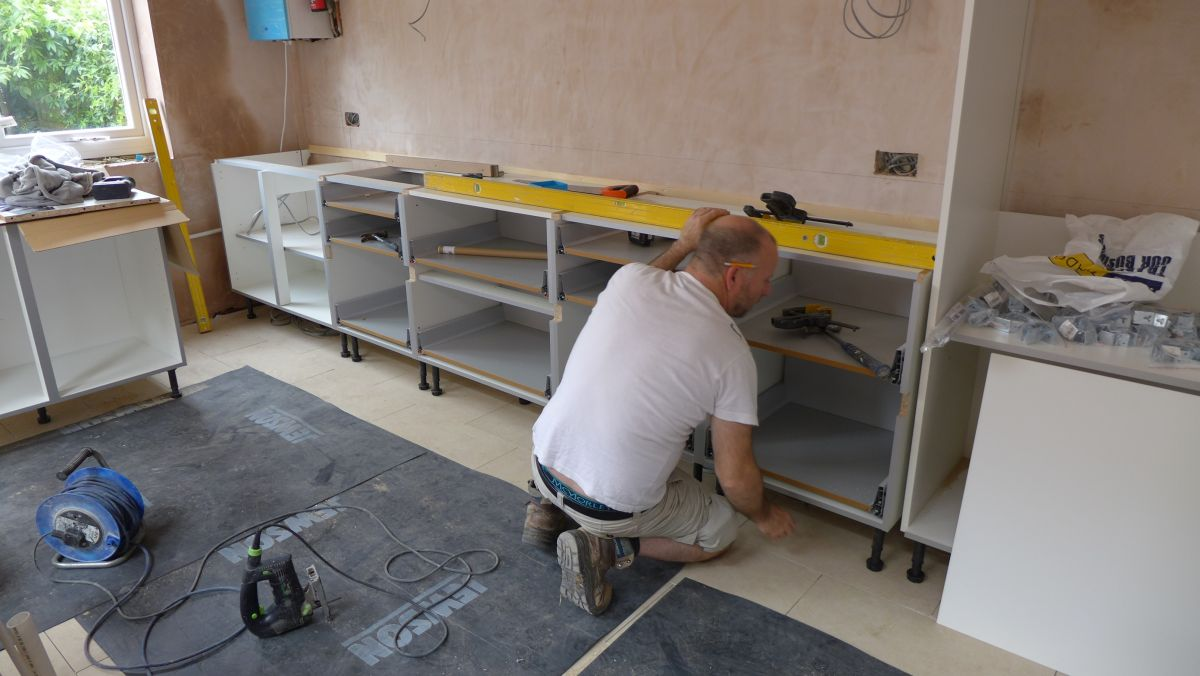 fitting a new kitchen - the joiner levels up the units