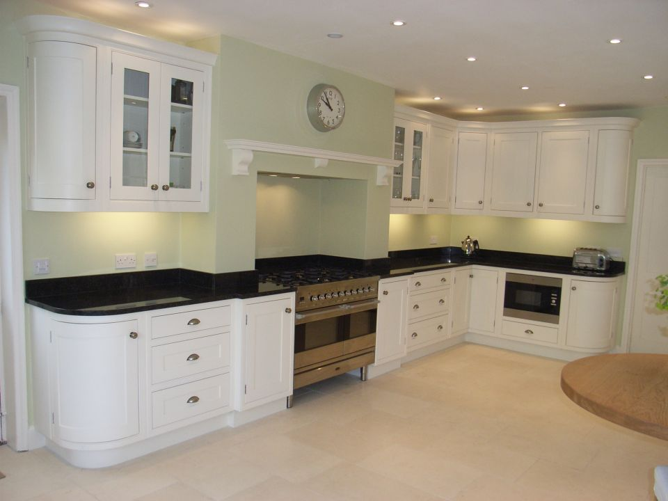 a look at kitchen decoration and how to coordinate all the colours and finishes in a kitchen. Here we team pale green walls with ivory white cabinets and black granite