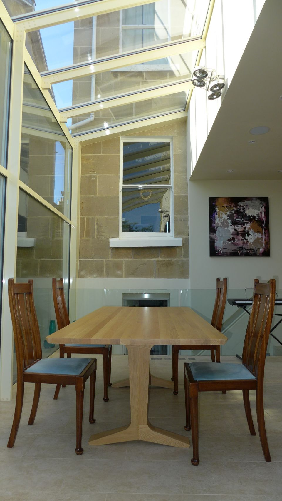 cantilevered lights over the dining table in glass conservatory