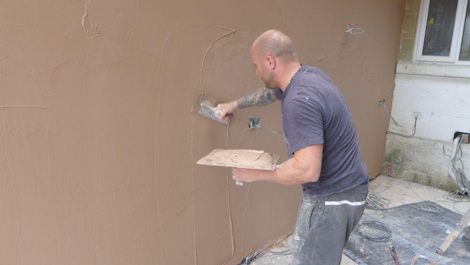 plastering walls and ceilings - here he is applying the skim coat