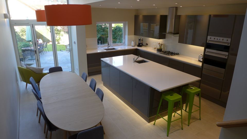kitchen island sits centrally in this grey and white kitchen design.